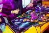 man in purple shirt behind dj equipment