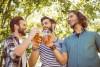 bearded men drinking beer outside