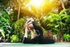 girl doing yoga on a patio surrounded by tropical trees